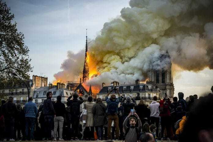 People watch the landmark cathedral burning in central Paris
