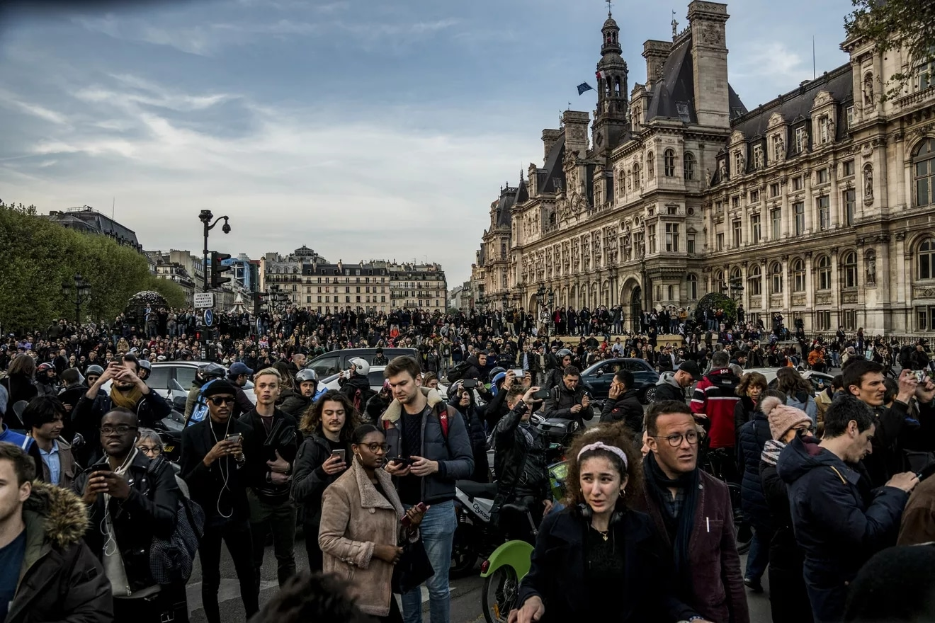 Hundreds gather in central Paris to watch smoke and flames rise at the cathedral.