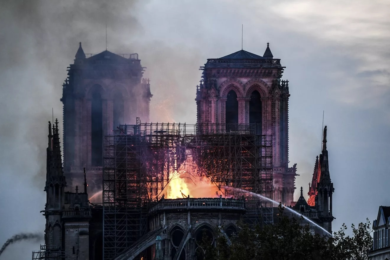 Firefighters douse flames and smoke billowing from the roof of the cathedral