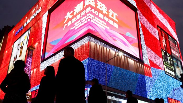 People stroll through a shopping district in the southern city of Shenzhen. Tax cuts will be one of the methods used to support the Chinese economy.
