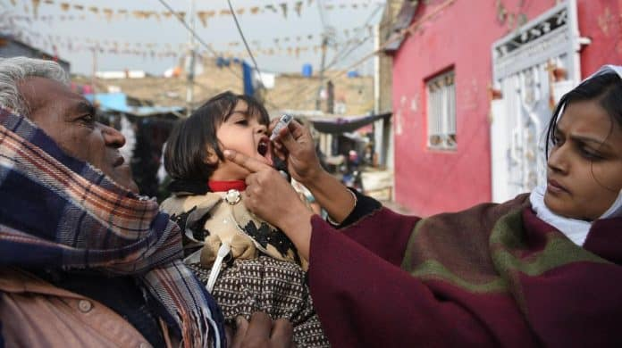 A Pakistani health worker administers polio vaccine drops to a child during a polio vaccination campaign in Islamabad on December 12, 2018.